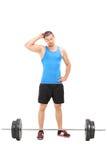Atleta de sexo masculino dudoso que mira un barbell Imagen de archivo