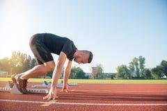 Atleta de sexo masculino en la posición de salida en la pista corriente del atletismo fotos de archivo libres de regalías