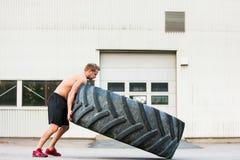 Atleta de sexo masculino Flipping Large Tire fotos de archivo libres de regalías