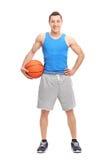 Atleta de sexo masculino joven que lleva a cabo un baloncesto Fotos de archivo libres de regalías