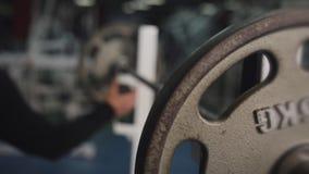 Atleta de sexo masculino joven Raises The Barbell que miente en el gimnasio almacen de video