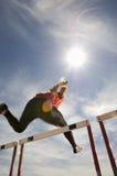 Atleta de sexo masculino Jumping Hurdle Fotos de archivo libres de regalías