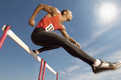 Atleta de sexo masculino Jumping Over obstáculos Imagen de archivo
