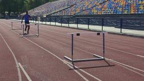 Atleta de sexo masculino profesional que supera fácilmente los obstáculos, carrera de vallas, entrenamiento metrajes