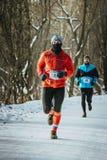 Atleta de sexo masculino que corre abajo de un callejón nevoso en bosque Imagenes de archivo