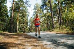Atleta de sexo masculino que corre abajo del camino en bosque Fotos de archivo libres de regalías