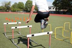 Atleta de sexo masculino que salta sobre obstáculos Imagen de archivo libre de regalías