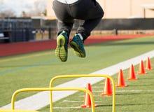 Atleta de sexo masculino que salta sobre obstáculos amarillos Fotos de archivo libres de regalías