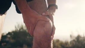 Atleta de sexo masculino que sostiene la rodilla dolorosa almacen de video