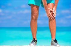 Atleta de sexo masculino que sufre de dolor en pierna mientras que Foto de archivo