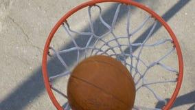 Atleta de sexo masculino que tira una bola a través de la cesta, jugador de básquet profesional almacen de video