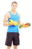 Atleta de sexo masculino sonriente que lleva a cabo pesa de gimnasia y plato lleno de veg fresco fotografía de archivo