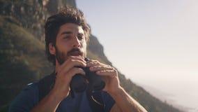Atleta de sexo masculino sonriente Standing Against Mountain almacen de video