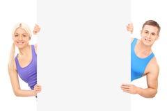 Atleta de sexo masculino y de sexo femenino que se coloca detrás del panel Imagen de archivo