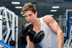 Atleta de sorriso novo que levanta peso no gym Imagens de Stock Royalty Free