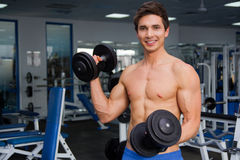 Atleta de sorriso novo que levanta peso no gym Fotografia de Stock