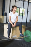 Atleta de sorriso Sitting On Box pelo Barbell no health club Foto de Stock Royalty Free