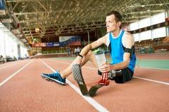 Atleta deficiente Resting na pista de atletismo imagem de stock