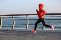 Atleta del corredor de la mujer de la aptitud que corre en el camino de la playa Fotografía de archivo libre de regalías