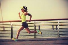 Atleta del corredor de la mujer de la aptitud que corre en el camino de la playa Imágenes de archivo libres de regalías
