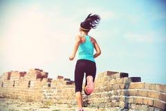 Atleta del corredor de la mujer que corre en rastro en la Gran Muralla china Imagenes de archivo