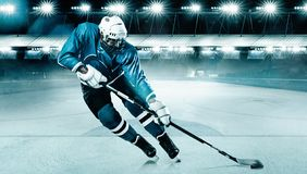 Atleta del giocatore di hockey su ghiaccio nel casco e guanti sullo stadio con il bastone Colpo di azione Concetto di sport immagini stock libere da diritti