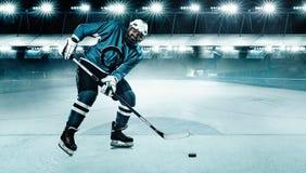 Atleta del giocatore di hockey su ghiaccio nel casco e guanti sullo stadio con il bastone Colpo di azione Concetto di sport fotografie stock libere da diritti
