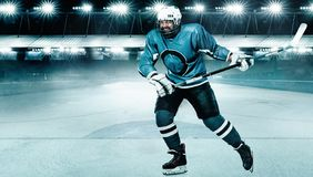 Atleta del giocatore di hockey su ghiaccio nel casco e guanti sullo stadio con il bastone Colpo di azione Concetto di sport fotografie stock