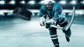 Atleta del giocatore di hockey su ghiaccio nel casco e guanti sullo stadio con il bastone Colpo di azione Concetto di sport immagini stock