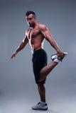 Atleta del hombre joven que hace ejercicios de los estiramientos Imágenes de archivo libres de regalías