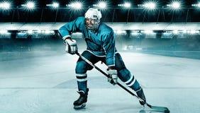 Atleta del jugador del hockey sobre hielo en el casco y guantes en estadio con el palillo Tiro de la acción Concepto del deporte imagen de archivo