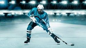 Atleta del jugador del hockey sobre hielo en el casco y guantes en estadio con el palillo Tiro de la acción Concepto del deporte foto de archivo libre de regalías