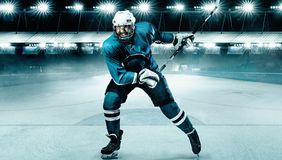 Atleta del jugador del hockey sobre hielo en el casco y guantes en estadio con el palillo Tiro de la acción Concepto del deporte imagen de archivo libre de regalías