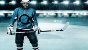 Atleta del jugador del hockey sobre hielo en el casco y guantes en estadio con el palillo Tiro de la acci?n Concepto del deporte fotografía de archivo libre de regalías