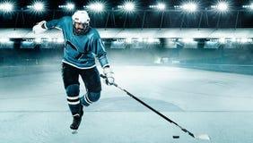 Atleta del jugador del hockey sobre hielo en el casco y guantes en estadio con el palillo Tiro de la acci?n Concepto del deporte fotos de archivo