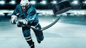 Atleta del jugador del hockey sobre hielo en el casco y guantes en estadio con el palillo Tiro de la acci?n Concepto del deporte imagen de archivo
