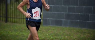 Atleta del viejo hombre que corre por maratón del parque de la ciudad del verano fotos de archivo