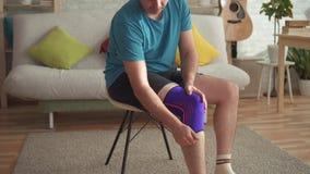 Atleta dell'uomo che prepara per la formazione, con una fasciatura sul suo ginocchio video d archivio