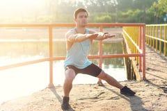 Atleta dell'uomo di forma fisica che si scalda le gambe prima del pareggiare all'aperto Fotografia Stock Libera da Diritti