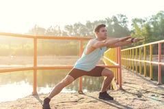 Atleta dell'uomo di forma fisica che si scalda le gambe prima del pareggiare all'aperto Fotografia Stock