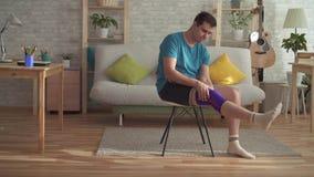 Atleta dell'uomo dopo che la lesione mette una fasciatura sul ginocchio archivi video