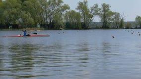 Atleta dell'uomo sul kajak di rematura sul lago archivi video