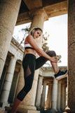 Atleta della donna che fa allenamento di forma fisica che prende supporto di una colonna di pietra Donna di forma fisica che fa a immagine stock libera da diritti