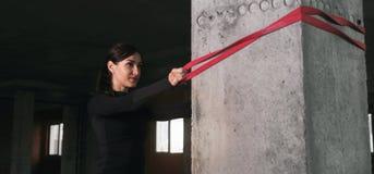 Atleta della donna che fa esercizio con gli sport di gomma in palestra Fotografia Stock
