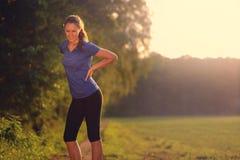 Atleta della donna che fa una pausa per alleviare il suo dolore alla schiena Immagini Stock Libere da Diritti