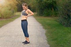 Atleta della donna che fa una pausa per alleviare il suo dolore alla schiena Fotografie Stock Libere da Diritti
