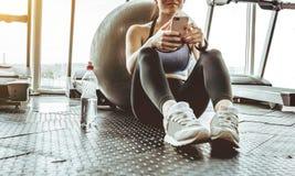 Atleta della giovane donna che per mezzo del telefono cellulare alla palestra immagine stock