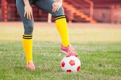 Atleta della giovane donna che posa con una palla sul primo piano del campo di football americano immagine stock