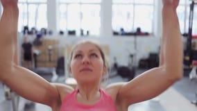 Atleta della giovane donna tirato su sulla barra Bella e ragazza atletica che lavora se stessa, agli sport ed allo stile di vita  video d archivio
