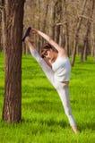 Atleta della ragazza che fa allungamento in un albero sull'erba Fotografie Stock